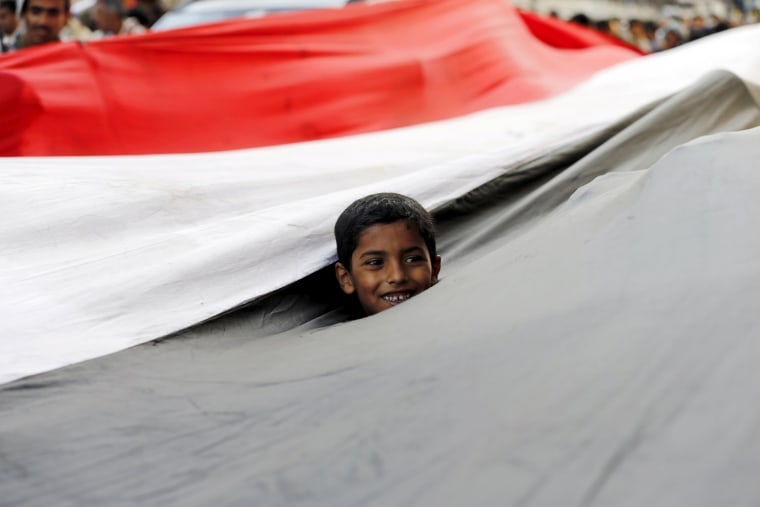 Image: A boy looks out from a Yemeni national flag as he takes part in a demonstration held by Houthi supporters against Saudi-led air strikes in Sanaa