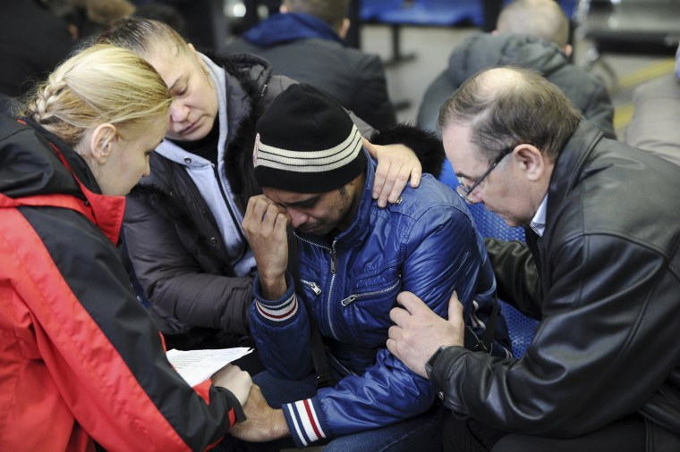 Image: A psychologist of the Russian Emergencies Ministry speaks with a relative of a victim of the crashed Flydubai Boeing 737-800 Flight FZ981 at the airport of Rostov-On-Don, Russia