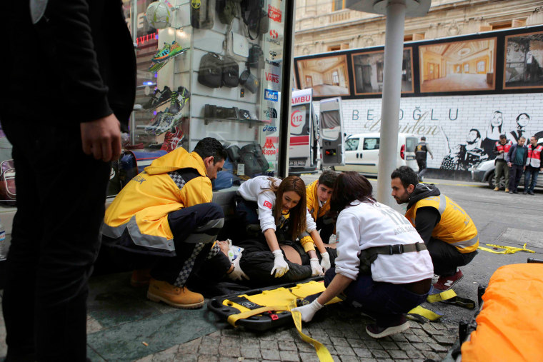 Image: Man is helped by emergency services members following a suicide bombing in central Istanbul