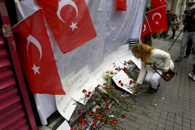 Image: A woman places carnations and a candle at the scene of a suicide bombing at Istiklal street