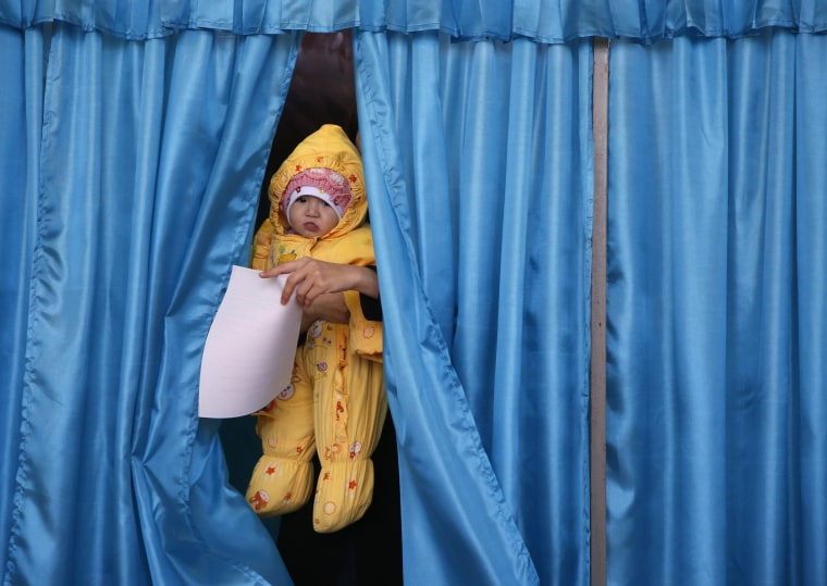 Image: A baby is carried out from a voting cabin by a woman voter at a polling station
