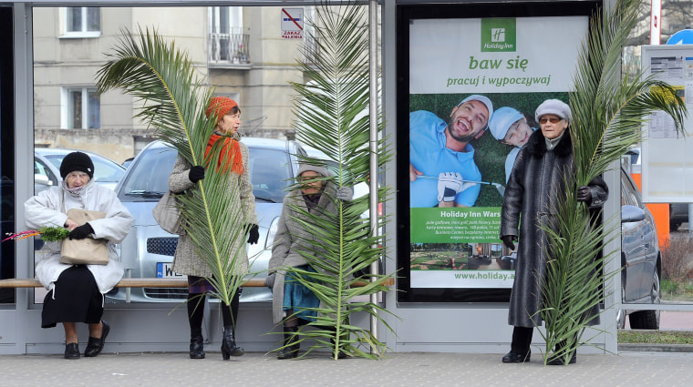 Image: Women with palm leaves wait at a bus stop after a Palm Sunday procession