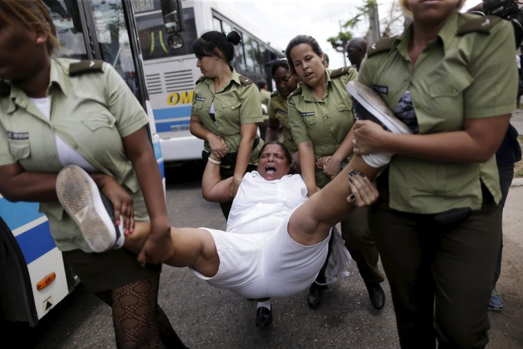 Image: A member of the 'Ladies in White' dissident group shouts as she is carried away by police officers in Havana
