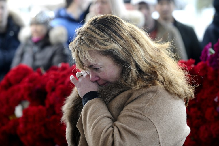 Image: A woman mourns after putting flowers in memory for the victims of the crashed FlyDubai plane