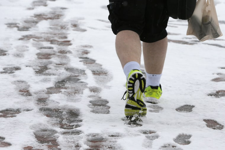 Image: A pedestrian wears shorts while walking on Boston Common during a snow storm on the second day of spring in Boston
