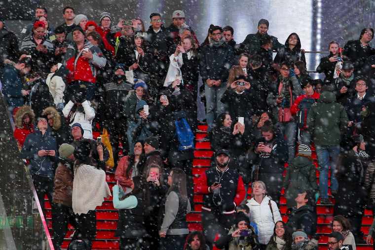 Image: People try to take pictures in Times Square as snow falls down during the first day of spring in New York