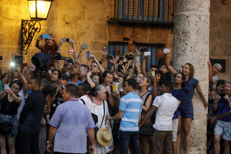 Image: Tourists and local residents take pictures as President Barack Obama tours Old Havana