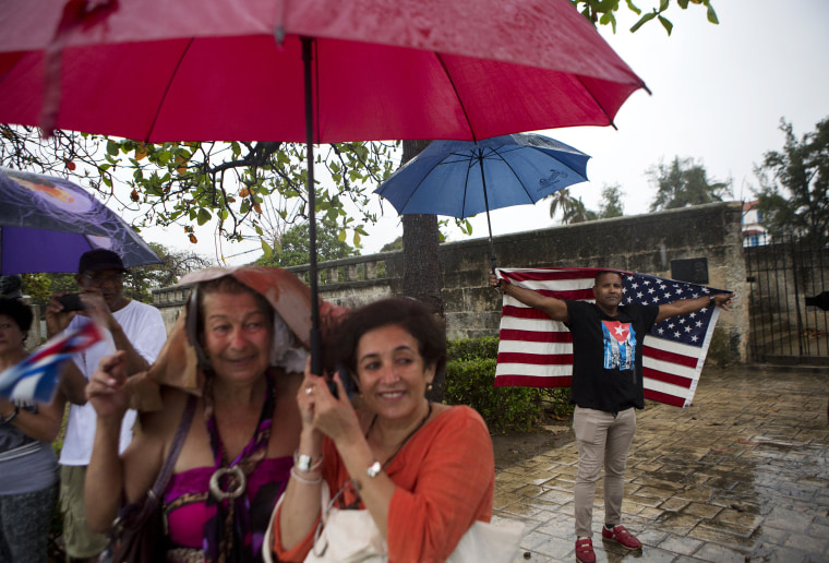 Image: A handful of Cubans gather along the Malecon sea wall under a steady rain