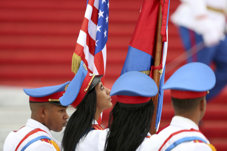 Image: Honor guards carry the U.S. and Cuban flags as they stand at the bottom of the stairs of the Revolution Palace during a visit by U.S. President Barack Obama in Havana