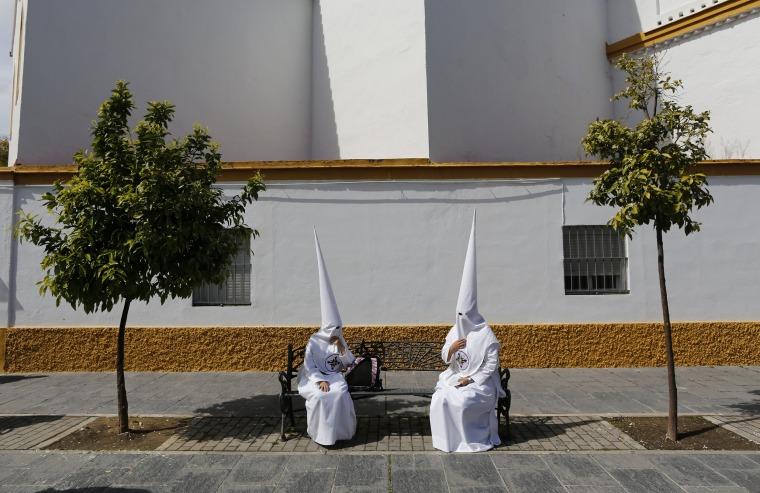 Image: Penitents of San Gonzalo brotherhood sit as they wait to take part in a Holy Week procession in the Andalusian capital of Seville, southern Spain