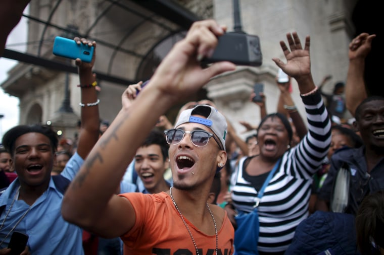 Image: People react as they wait for an eventual visit of U.S. President Barack Obama to downtown Havana