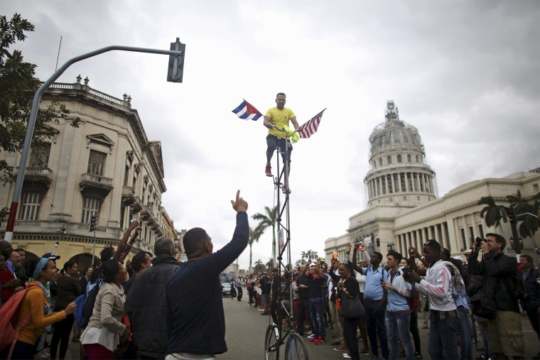 Image: A man pedals a bicycle displaying the U.S. and Cuban flags near the Capitol, as people wait for an eventual visit of U.S. President Barack Obama to downtown Havana
