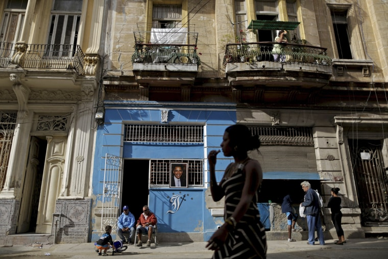 Image: People are seen near a picture of U.S. President Barack Obama in Havana