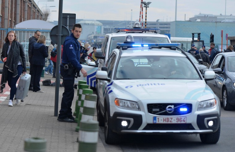 Image: Police officers stand guard around the Zaventem Airport after two explosions went off