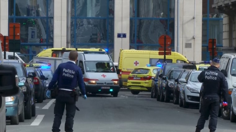 Image: Emergency personnel are seen at the scene of a blast outside a metro station in Brussels