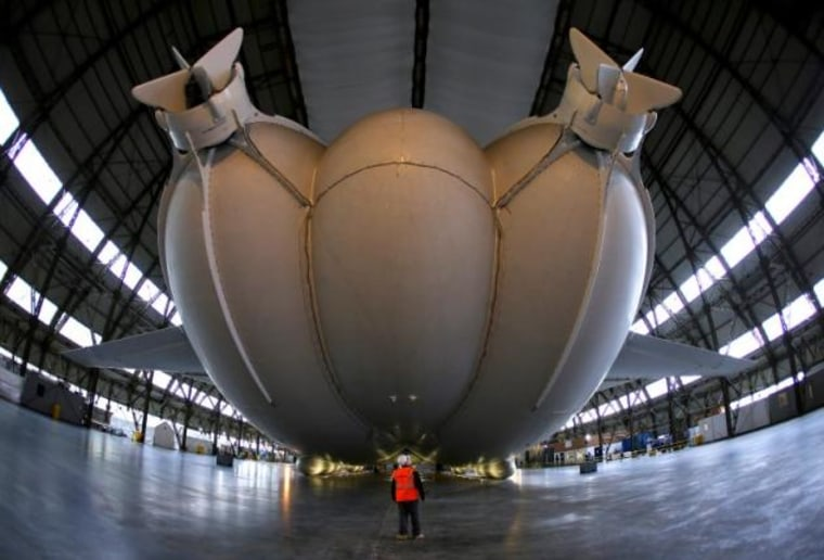 A worker stands under the Airlander 10 hybrid airship during its unveiling in Cardington