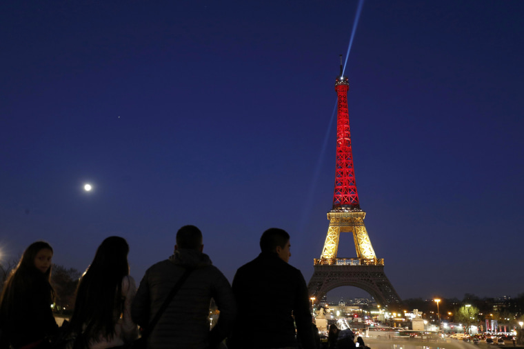 Image: The Eiffel Tower is seen with the black, yellow and red colours of the Belgian flag in tribute to the victims of today's Brussels bomb attacks in Paris