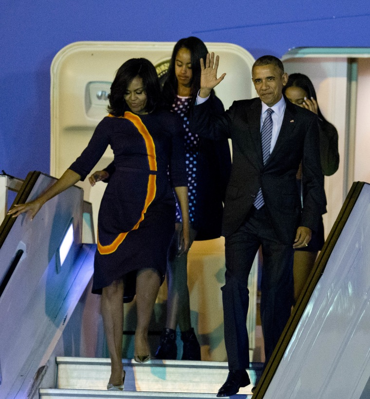 President Barack Obama waves from Air Force One as he arrives accompanied by first lady Michelle and daughters Sasha, behind right, and Malia at the international Buenos Aires airport, Argentina, early Wednesday, March 23, 2016.