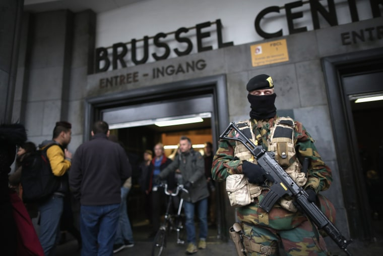 Image: Armed soldiers guard the entrance to Brussels Central Station