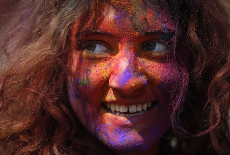 Image: A woman with coloured powder smeared on her face smiles as she celebrates Holi, the Festival of Colours, in Kathmandu