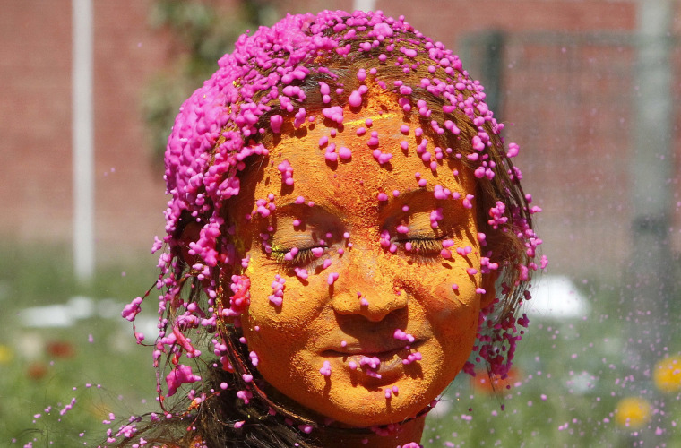 Image: A students with her face smeared in coloured powder, celebrates Holi at a university campus in Chandigarh