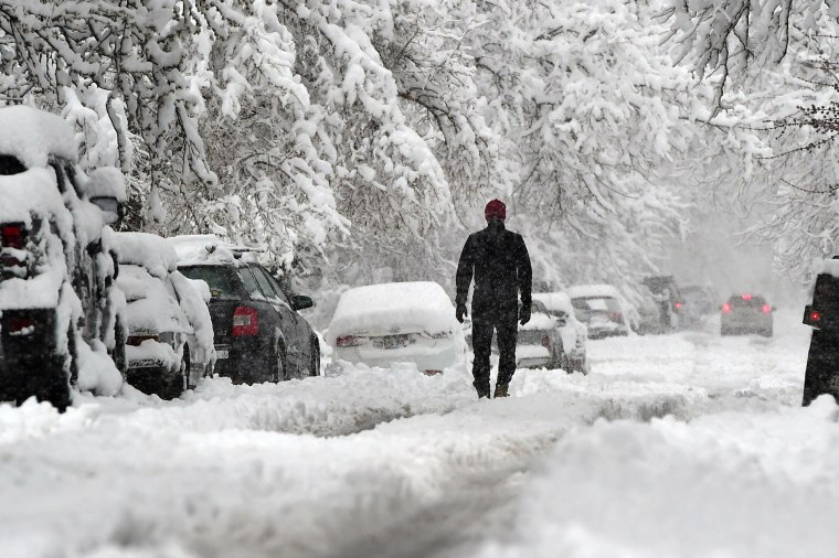Image: A man walks down a street in Boulder, Colo.