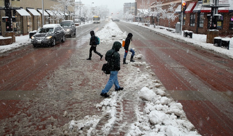 Image: Pedestrians cross a slushy road as a spring snow storm passes over Boulder, Colo.
