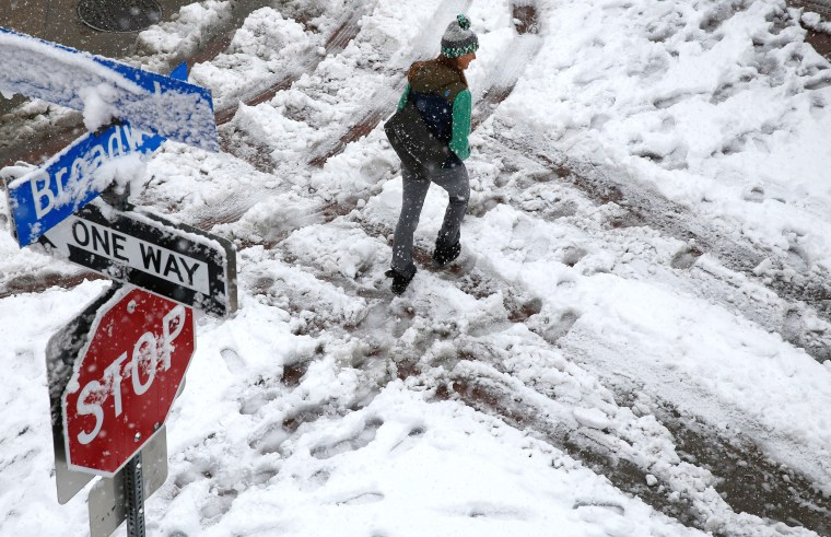 Image: A pedestrian walks through slush as a spring snow storm passes over Boulder, Colo.
