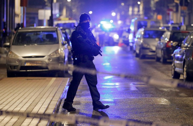 Image: A masked Belgian police takes part in police operations in Schaerbeek