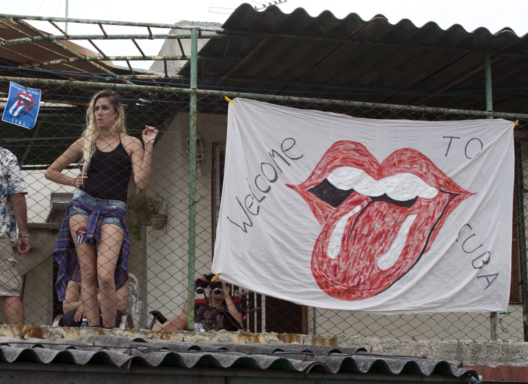 A woman stands on the roof of a house next to the Ciudad Deportiva to get a view of the Rolling Stones concert in Havana, Cuba.