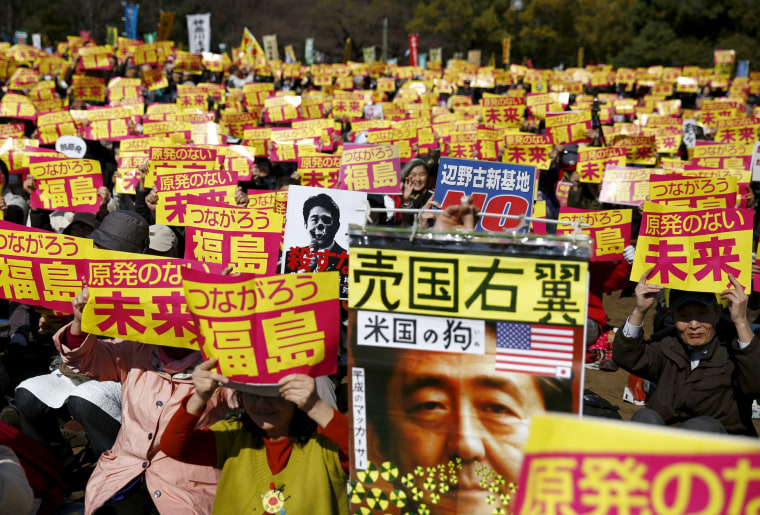 Image: People hold placards with anti-nuclear energy slogans during a protest calling for a nuclear-free future in Tokyo