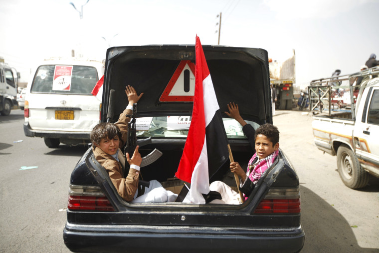 Image: Houthi followers sit on the back of car with Yemen's national flag before they attend a rally marking one year of Saudi-led air strikes, in Yemen's capital Sanaa