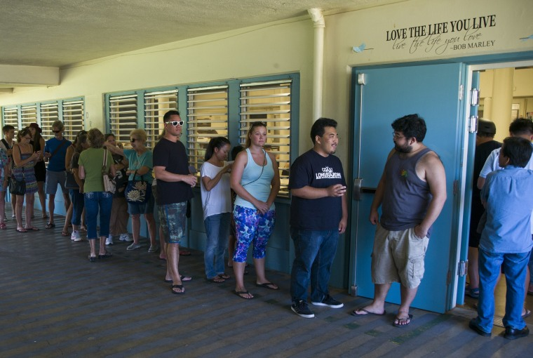 Voters line up outside a polling station set up at Kailua Intermediate School to register to vote in Hawaii's Democratic primary, Saturday, March 26, 2016, in Kailua, Hawaii.