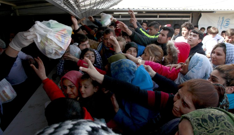 Image: Refugees and migrants reach for food packages provided by humanitarian workers