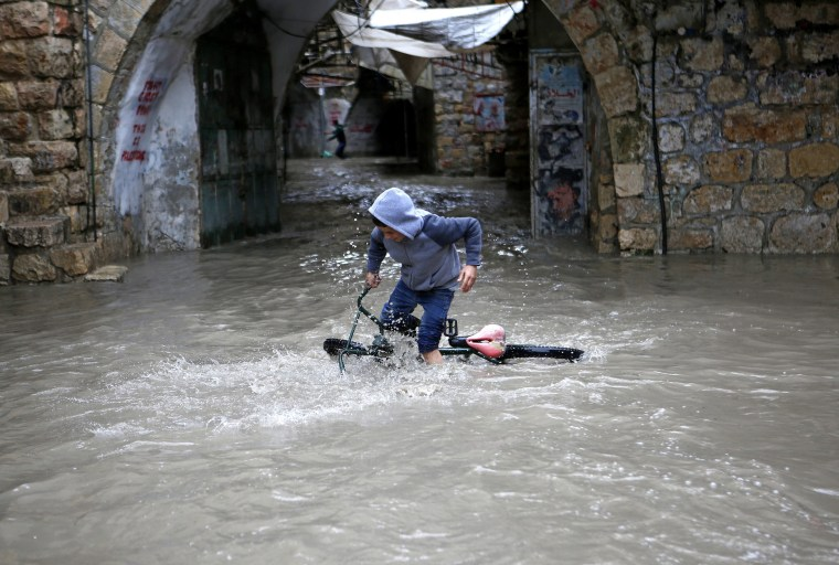 Image: A Palestinian boy tries to ride his bicycle through flood water