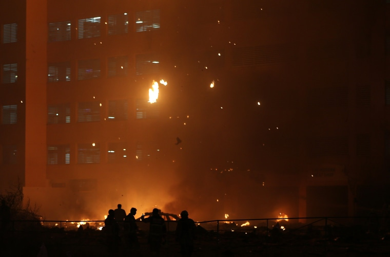 Image: Debris falls from a high-rise building as a fire spreads up the side of the building in Ajman