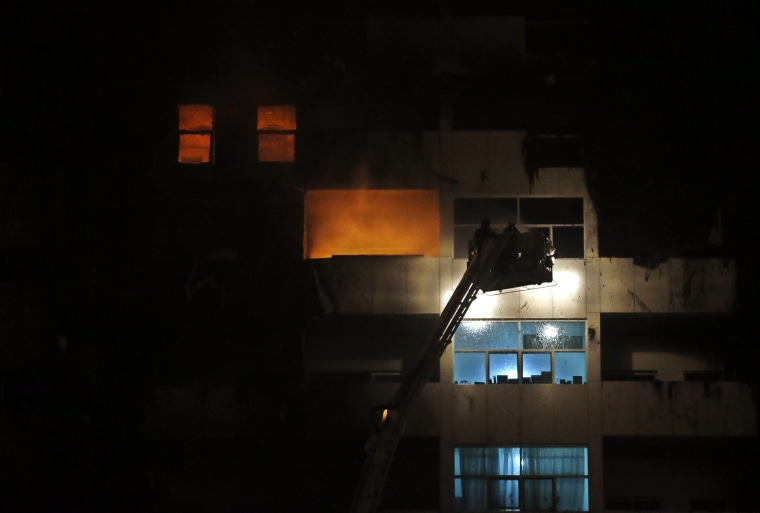Image: Members of the Civil Defense and fire services extinguish a fire at residential buildings at al-Sawan area