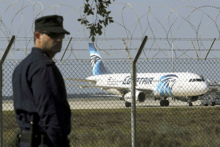 Image: A policeman stands guard at the airport near a hijacked plane