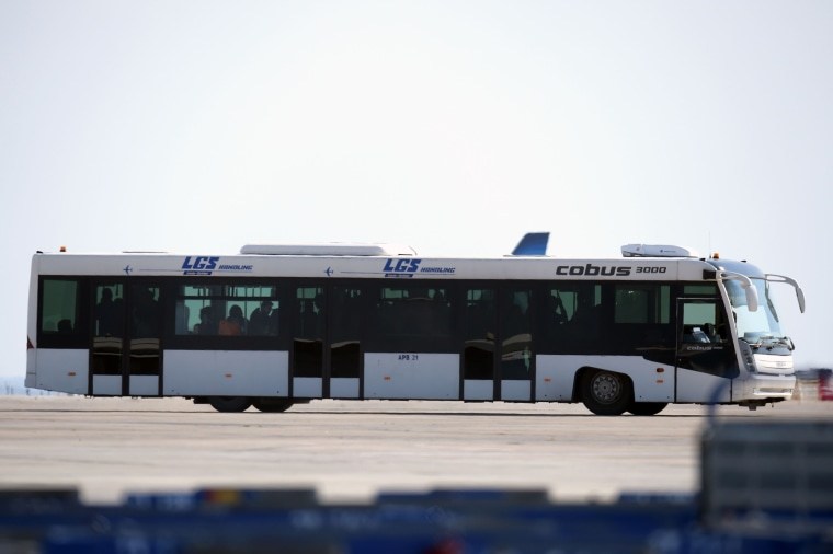 Image: A bus carrying passengers from the plane is seen driving away
