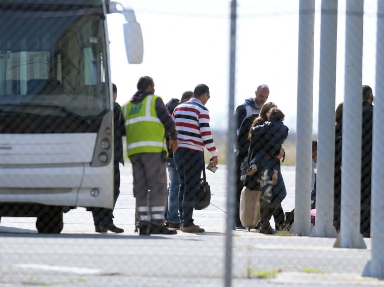 Image: Passengers leave the bus  after disembarking the plane