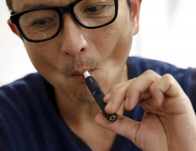 "A customer tries a Philip Morris' ""iQOS"" smokeless tobacco at an iQOS store in Tokyo"