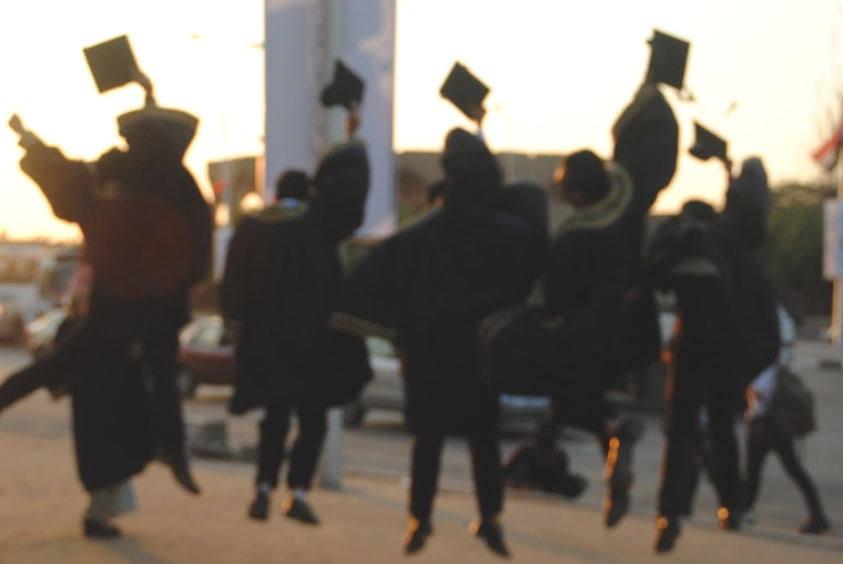 Rear View Of Excited Students Throwing Mortarboard During Graduation