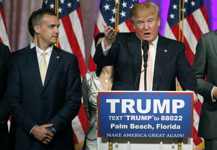 Image: Campaign manager Corey Lewandowski stands next to Donald Trump during a news conference in Palm Beach, Florida