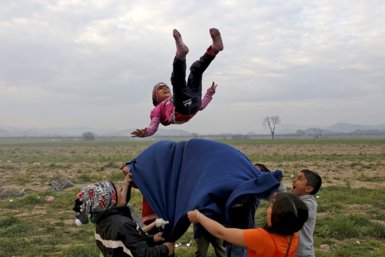 Image: Children play at a makeshift camp for migrants and refugees at the Greek-Macedonian border near the village of Idomeni