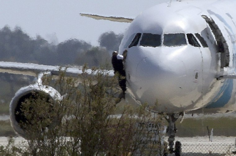 Image: A man climbs out of the cockpit window of the hijacked Egyptair Airbus A320 at Larnaca Airport in Larnaca, Cyprus