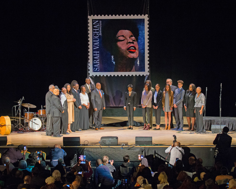 Participants gather on stage following stamp unveiling for late jazz singer Sarah Vaughan