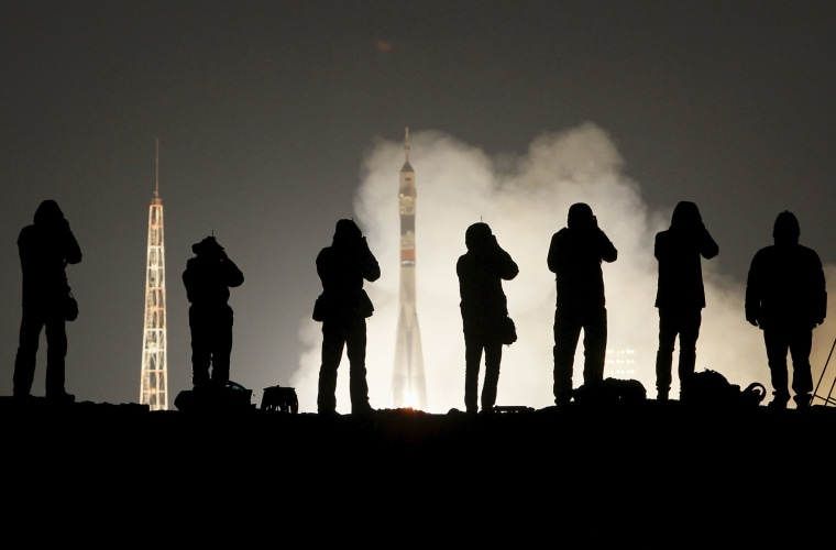 Image: Photographers take pictures as the Soyuz TMA-20M spacecraft carrying the International Space Station (ISS) crew blasts off to the International Space Station (ISS) from the launchpad at the Baikonur cosmodrome, Kazakhstan
