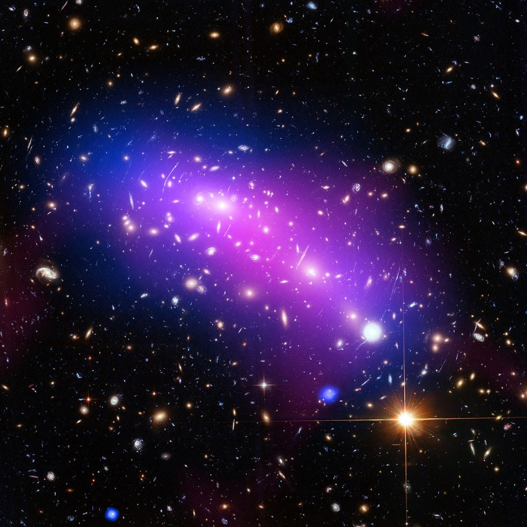 Image: A multi-coloured haze which marks the site of two colliding galaxy clusters is seen in a NASA image
