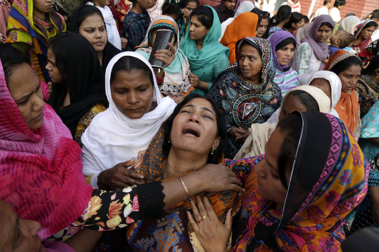 Image: People try to comfort a Pakistani Christian mother during the funeral of her two daughters