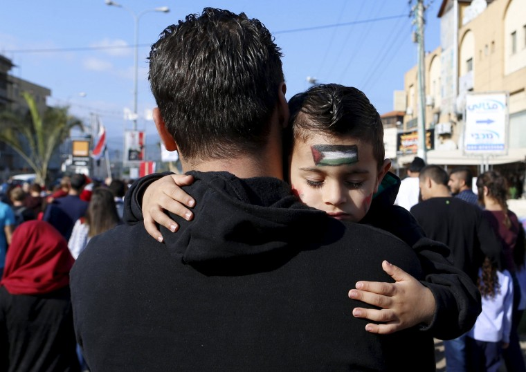 Image: An Israeli Arab boy sleeps as his father carries him during a Land Day rally in the northern Israeli village of Arrabe
